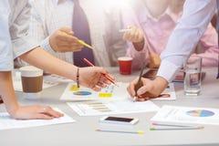 Geschäfts-Teamvernetzung - Bürotisch mit Diagrammen und den Leute-Händen stockbilder