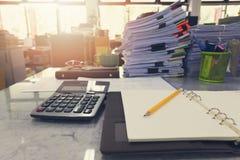 Geschäfts- und Finanzkonzept des Bleistifts und des Notizbuches auf Schreibtisch mit Stapel Geschäftspapier lizenzfreies stockbild