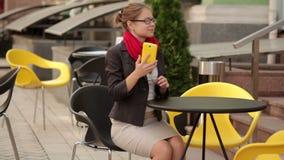 Geschäfts- und Lebensstilkonzept - lächelnde junge Frau in den Brillen um Smartphone am Café ersuchend stock footage