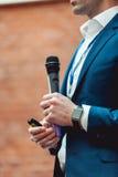 Geschäfts- und Sprachethema: Mann in einer blauen Klage, die ein graues Mikrofon a auf einem orange Ziegelsteinhintergrund hält Lizenzfreie Stockfotos