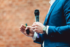 Geschäfts- und Sprachethema: Mann in einer blauen Klage, die ein graues Mikrofon a auf einem orange Ziegelsteinhintergrund hält Lizenzfreies Stockbild