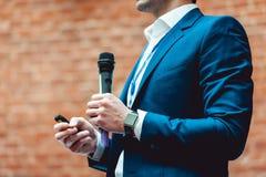 Geschäfts- und Sprachethema: Mann in einer blauen Klage, die ein graues Mikrofon a auf einem orange Ziegelsteinhintergrund hält Stockfotografie