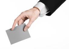 Geschäfts- und Werbungsthema: Bemannen Sie im schwarzen Anzug, der in der Hand eine graue leere Karte lokalisiert auf weißem Hint Stockfotografie