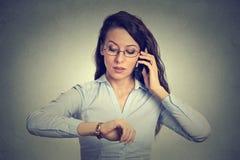 Geschäfts- und Zeitmanagementkonzept Geschäftsfrau, die Armbanduhr betrachtet lizenzfreies stockfoto
