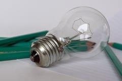 Geschäfts-Zusammensetzung mit Glühlampe mit Notizbuch und Bleistiften Lizenzfreies Stockfoto