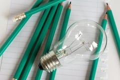 Geschäfts-Zusammensetzung mit Glühlampe mit Notizbuch und Bleistiften Lizenzfreie Stockbilder