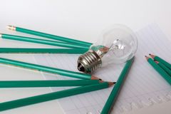 Geschäfts-Zusammensetzung mit Glühlampe mit Notizbuch und Bleistiften Lizenzfreies Stockbild