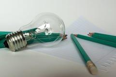 Geschäfts-Zusammensetzung mit Glühlampe mit Notizbuch und Bleistiften auf Hintergrund Stockfotografie
