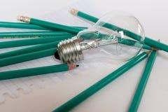 Geschäfts-Zusammensetzung mit Glühlampe mit Notizbuch und Bleistiften auf Hintergrund Stockbild