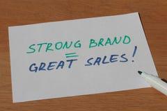 Geschäftsanmerkung über große Verkäufe der starken Marke mit Stift Stockfotos