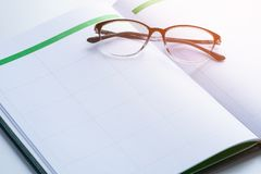 Geschäftsanzeigenkonzept mit Terminkalender, Gläser Lizenzfreies Stockbild