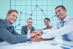 Geschäftsarbeitskräfte erfassen ihre Hände zusammen während einer Sitzung vor digitalem Schirm mit graphi Stockfotos