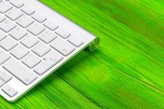 Geschäftsarbeitsplatz mit Computer, drahtlose Tastatur, Schlüssel auf altem grünem Holztischhintergrund Schreibtisch mit Kopien-R Lizenzfreie Stockbilder