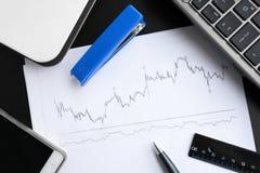 Geschäftsarbeitsplatz mit Papieren mit Diagrammen Lizenzfreie Stockfotos