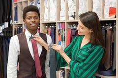 Geschäftsberater, der auf Krawatte für Kunden in der Boutique versucht stockbild
