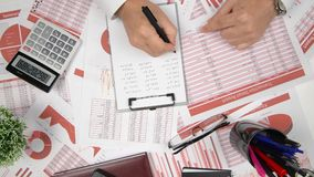 Geschäftsberichte, Datentabellen und Diagramme - direkt über Ansicht des Bürotischarbeitsplatzes stock video