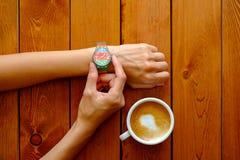 Geschäftsdame, die auf Uhr im Café aufpasst Lizenzfreie Stockfotos