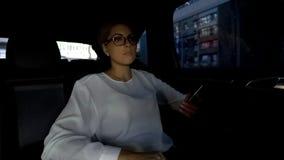 Geschäftsdame, die Smartphone in den Händen, sitzend auf Rücksitze im Luxusauto hält lizenzfreie stockbilder