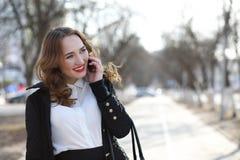 Geschäftsdame in einer Klage draußen mit Handy lizenzfreies stockfoto