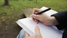 Geschäftsdame hebt einen wichtigen Wochentag in einem Notizbuch mit einem schwarzen Gelschreiber hervor stock video footage