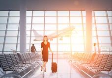 Geschäftsdame im schwarzen Anzug im Flughafen Stockfoto