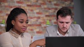Geschäftsdame sagt dem Geschäftsmann den Informationen über die Arbeit, der auf dem Laptop schaut stock video