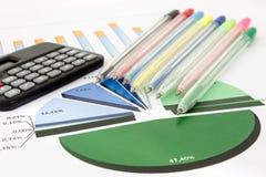 Geschäftsdiagramm mit Taschenrechner und Stiften stockfotografie