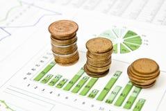 Geschäftsdiagramme und -münzen Stockfotografie