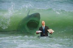 Geschäftsdruckmann, der Schlag durch Welle mit angreifendem Haifisch erhält stockfoto