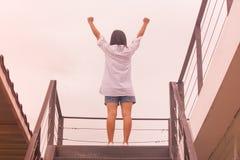 Geschäftserfolg-Konzept: Die Asiatin, die auf Treppe steht und heben oben ihre Hände an stockfotografie