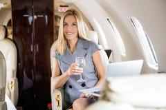 Geschäftsflugzeug Geschäftsfrau-Having Wine Ins lizenzfreies stockfoto