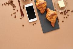 Geschäftsfrühstück von zwei französischen Hörnchen mit Smartphone Stockbild