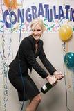 Geschäftsfrauöffnungsflasche Champagner lizenzfreie stockfotos