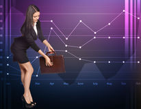 Geschäftsfrau öffnet den Aktenkoffer, der auf a steht Lizenzfreies Stockbild