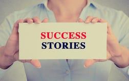 Geschäftsfrau übergibt das Halten des Kartenzeichens mit Erfolgsgeschichtetextnachricht Lizenzfreies Stockfoto