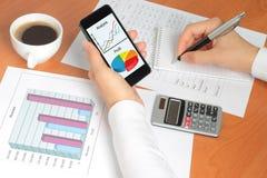 Geschäftsfrau arbeitet an ihrem Arbeitsplatz mit Smartphone Lizenzfreie Stockfotos