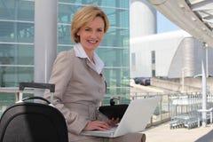 Geschäftsfrau außerhalb des Flughafens Stockbild