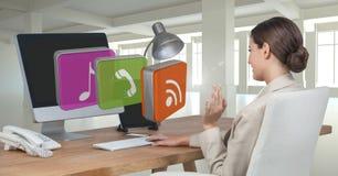 Geschäftsfrau auf Computer am Schreibtisch mit apps Ikonen im Büro Lizenzfreie Stockfotografie