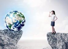 Geschäftsfrau auf Felsenberg mit einer Kugel Stockfotos