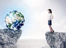 Geschäftsfrau auf Felsenberg mit einer Kugel Stockbild