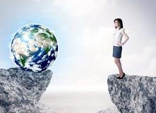 Geschäftsfrau auf Felsenberg mit einer Kugel Lizenzfreie Stockfotos