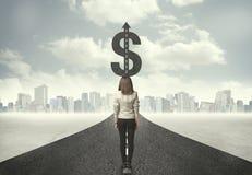Geschäftsfrau auf Straßenüberschrift in Richtung zu einem Dollarzeichen Stockbilder