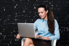 Geschäftsfrau auf Stuhl mit Laptop Stockfotografie