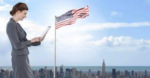 Geschäftsfrau auf Tablette mit amerikanischer Flagge im Stadtbild Stockbild
