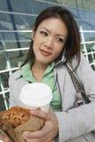 Geschäftsfrau beim Anruf, der zum Mitnehmen Nahrung hält Stockbild