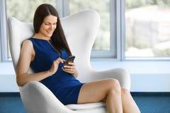 Geschäftsfrau benutzt Handy im Büro JPG + vektorabbildung Stockfotos