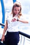 Geschäftsfrau betrachtet die Borduhr lizenzfreie stockfotografie