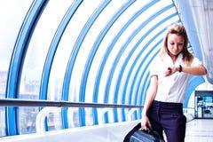 Geschäftsfrau betrachtet die Borduhr stockbild