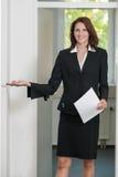 Geschäftsfrau bittet, hereinzukommen Stockfotografie