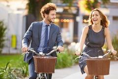 Geschäftsfrau-And Businessman Riding-Fahrrad durch Stadt-Park Stockbild